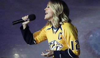 FILE - In this April 17, 2017 file photo, country music star Carrie Underwood performs the national anthem before Game 3 of a first-round NHL hockey playoff series between the Predators and the Chicago Blackhawks in Nashville, Tenn. Underwood is the wife of Predators center Mike Fisher.  The longtime anthem singer at Nashville Predators hockey games has sour grapes over being replaced in the Stanley Cup playoffs by superstar singers such as Carrie Underwood, Luke Bryan, Lady Antebellum and Little Big Town. (AP Photo/Mark Humphrey, File)