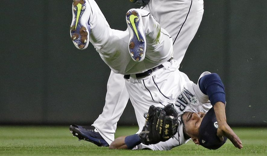 Seattle Mariners center fielder Jarrod Dyson tumbles after snagging a fly ball from Oakland Athletics' Khris Davis in the sixth inning of a baseball game Monday, May 15, 2017, in Seattle. (AP Photo/Elaine Thompson)