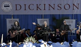 Musician Jon Bon Jovi, top center, performs with his band during a surprise appearance at the Fairleigh Dickinson University commencement ceremony, Tuesday, May 16, 2017, at MetLife Stadium in East Rutherford, N.J. The school won a nationwide contest to bring the New Jersey-based band Bon Jovi to play their graduation by generating the most interest on social media. (AP Photo/Julio Cortez)