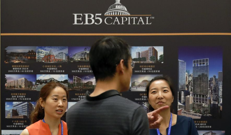In this May 7, 2017 photo, a man talks with representatives at an exhibitor booth at the Invest in America Summit held at a hotel in Beijing. The number of Chinese using investment migration programs worldwide tripled between 2010 and 2015, the AP found among the countries in its survey. (AP Photo/Andy Wong)