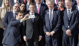 Co-president of Paris 2024 bid Tony Estanguet, front right, takes a selfie of the back row from left, International Olympic Committee Evaluation Commission Chair Patrick Baumann and new French President Emmanuel Macron, member of the IOC Guy Drut and co-president of the Paris 2024 bid Bernard Lapasset as they pose during a group photo at the Elysee palace in Paris, France, May 16, 2017. France's new President Emmanuel Macron is hosting the International Olympic Committee to try to boost Paris' bid to beat out Los Angeles in the heated race for the 2024 Games. (AP Photo/Michel Euler)