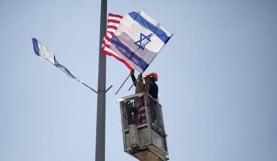 A worker hangs Israeli and American flags on a lamppost along a freeway leading to Jerusalem, days before a planned visit by President Donald Trump, Tuesday, May 16, 2017. The Israeli prime minister's office said it is seeking clarifications from Trump after an American official said the Western Wall is part of the West Bank. (AP Photo/Ariel Schalit)