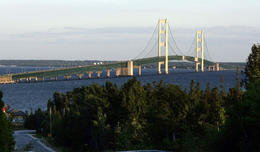 FILE- In this June 30, 2005, file photo, the Mackinac Bridge is seen from Saint Ignace, Mich. Michigan officials are banning most vehicles from the Mackinac Bridge during the annual Labor Day bridge walk because of concerns about terrorism. Tens of thousands of people join the annual walk across the nearly 5-mile-long bridge using two lanes on the bridge, while the other two have been reserved for vehicles. Under the policy announced Tuesday, May 16, 2017, the only vehicles allowed between 6:30 a.m. and noon will be buses carrying walkers. (AP Photo/Carlos Osorio, File)