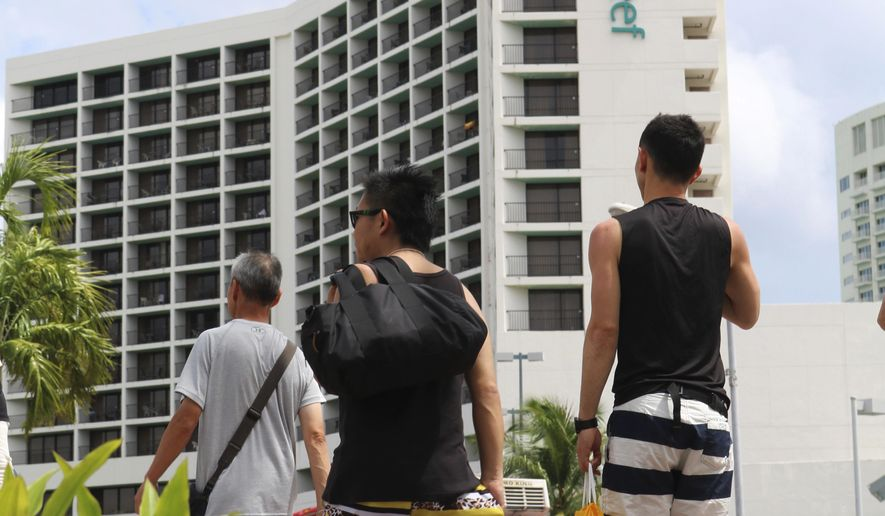 In this May 15, 2017 photo, tourists walk past a hotel in Tamuning, Guam on day the North Korea conducted its latest ballistic missile test. While most of the United States is still out of reach of a missile launched by North Korea, the U.S. territory of Guam, a key military hub in the Pacific, could be within range. That realization, coming after a missile launch over the weekend, had residents of the island casting a wary eye amid rising nuclear tensions between Pyongyang and Washington. Some worried they might find war at their doorstep, while others say they are more concerned about the potential loss of vital tourism dollars than they are a nuclear attack. (AP Photo/Haven Daley)