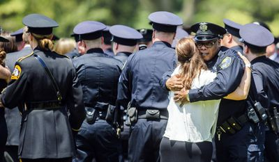 A police officer hugs a woman during the funeral for Norton Shores police officer Jonathan Ginka on Tuesday, May 16, 2017 in North Muskegon, Mich. Ginka was killed after his police cruiser struck a tree in the early morning hours of May 10 along Henry Street between Ross and Forest Park Roads in Norton Shores. (Kaytie Boomer /Muskegon Chronicle via AP)