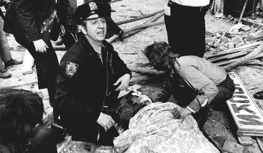 FILE- In this Jan. 24, 1975, file photo, a New York City police officer calls for help as he kneels near a victim of a bombing at the annex of Fraunces Tavern in New York. The leftist group Armed Forces of National Liberation, also known as FALN, claimed responsibility for the bombing that killed four people and injured more than 60. Puerto Rico nationalist and FALN leader, Jose Lopez Rivera, will be freed on Wednesday, May 17, 2017, after serving the longest prison time of any member of the violent separatist group that sought independence for the U.S. territory. (The Daily News via AP, File)