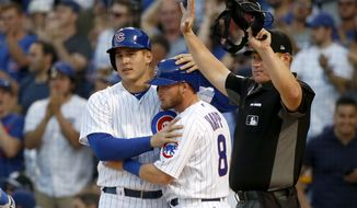 Chicago Cubs' Anthony Rizzo, left, celebrates with Ian Happ after they scored on a ground-rule double by Willson Contreras during the first inning of a baseball game against the Cincinnati Reds on Tuesday, May 16, 2017, in Chicago. Home plate umpire Tom Woodring calls time after the play. (AP Photo/Charles Rex Arbogast)