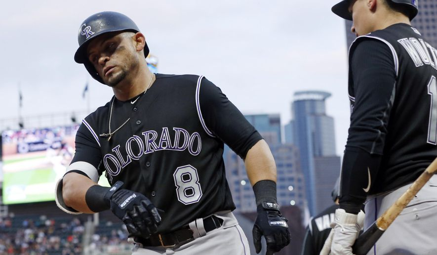 Colorado Rockies' Gerardo Parra, left, gets congratulated as he heads to the dugout on a solo home run off Minnesota Twins pitcher Phil Hughes in the fourth inning of a baseball game, Tuesday, May 16, 2017, in Minneapolis. (AP Photo/Jim Mone)