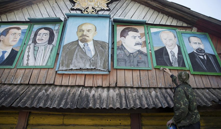 In this photo taken on Wednesday, May 3, 2017, Mikhail Korhunov paints the frames of his paintings, portraits of (from left): Russian Prime Minister Dmitry Medvedev, Russian czar Peter the Great, Soviet founder Vladimir Lenin, Soviet leader Josef Stalin, Russian President Vladimir Putin and Pyotr Stolypin, Russian prime minister from 1906 to 1911, at the top of Korhunov's house in the village of Severnaya Griva, about 130 kilometers (80 miles) east of Moscow, Russia. (AP Photo/Pavel Golovkin)