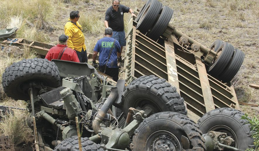 In this Sunday, May 14, 2017, photo, military personnel assess the scene of a tractor-trailer accident at the Highway 190/Daniel K. Inouye junction, about 25 miles northeast of Kailua-Kona, Hawaii. Army officials have identified the soldier who died when the military truck he was riding in crashed during training in Hawaii. (Laura Ruminski/West Hawaii Today via AP)