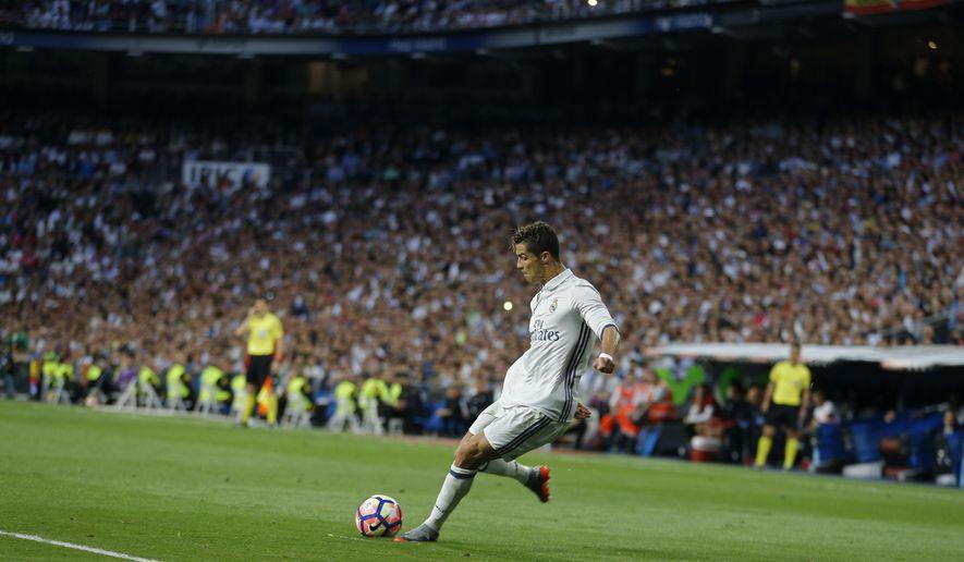 Real Madrid's Cristiano Ronaldo shoots a free kick during La Liga soccer match between Real Madrid and Sevilla at the Santiago Bernabeu stadium in Madrid, Sunday, May 14, 2017. Ronaldo scored twice in Real Madrid's 4-1 victory. (AP Photo/Francisco Seco)