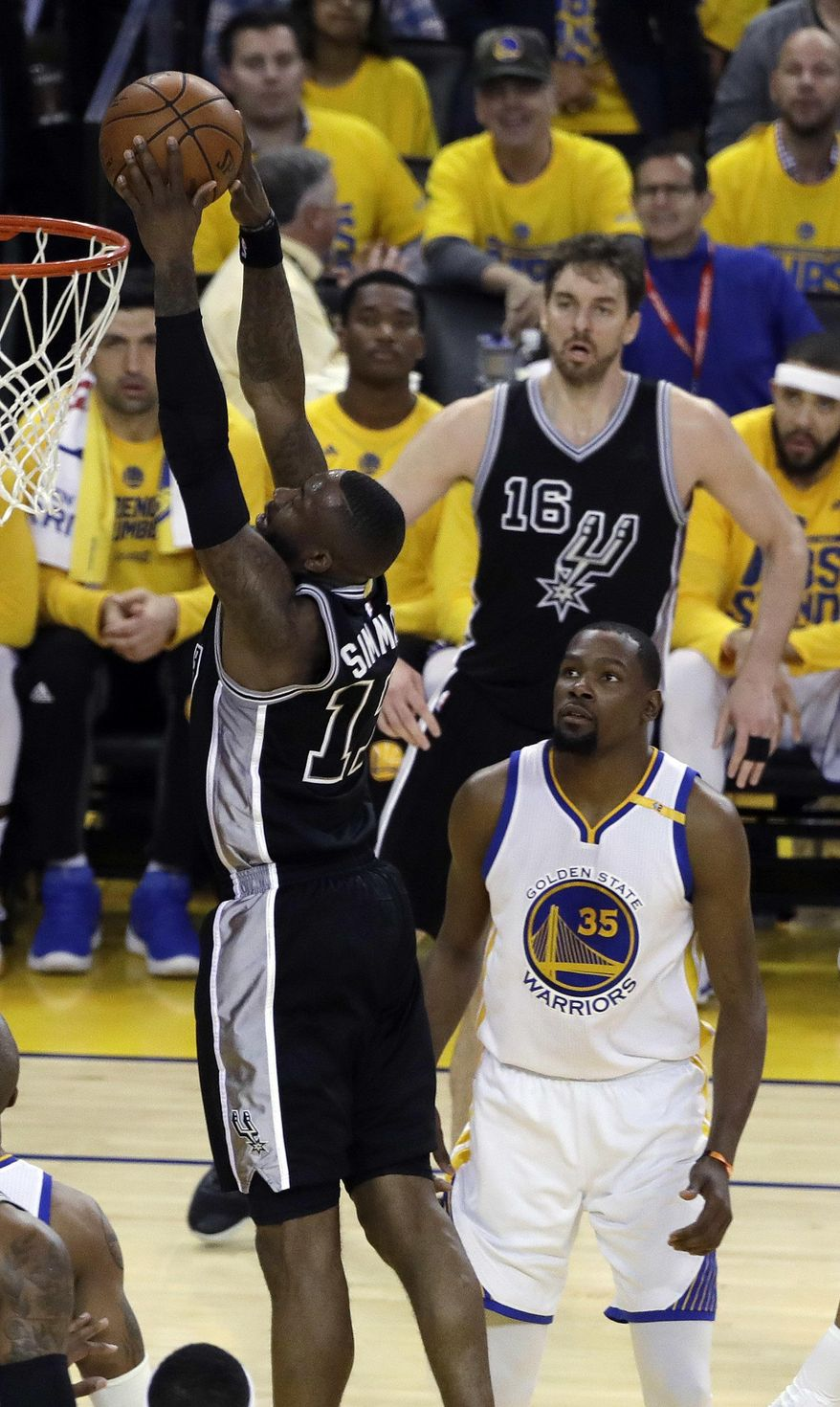 San Antonio Spurs' Jonathon Simmons, left, dunks past Golden State Warriors' Kevin Durant (35) during the first half of Game 2 of the NBA basketball Western Conference finals, Tuesday, May 16, 2017, in Oakland, Calif. (AP Photo/Marcio Jose Sanchez)