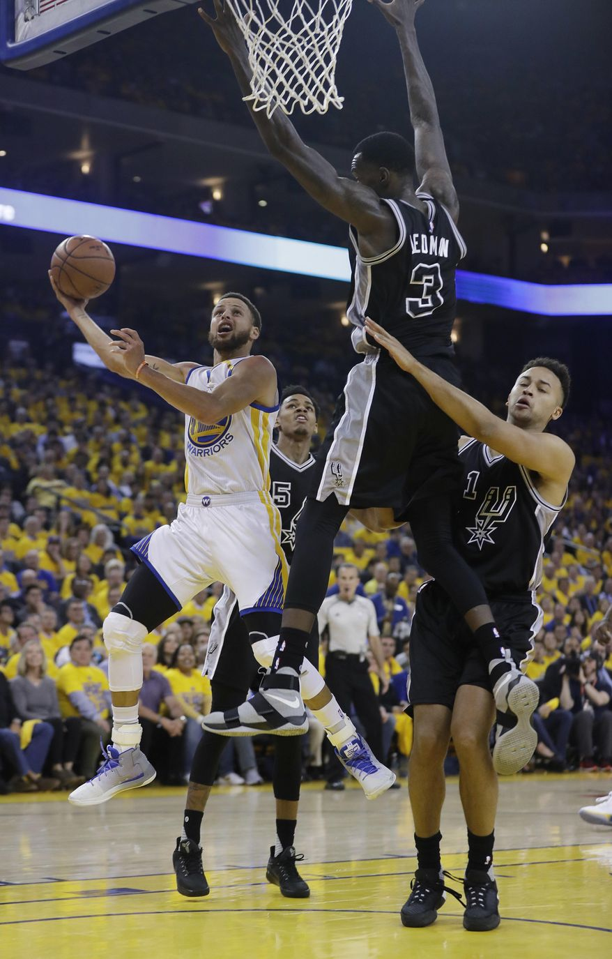 Golden State Warriors' Stephen Curry, left, drives past San Antonio Spurs' Dewayne Dedmon (3) and Kyle Anderson (1) during the first half of Game 2 of the NBA basketball Western Conference finals, Tuesday, May 16, 2017, in Oakland, Calif. (AP Photo/Marcio Jose Sanchez)