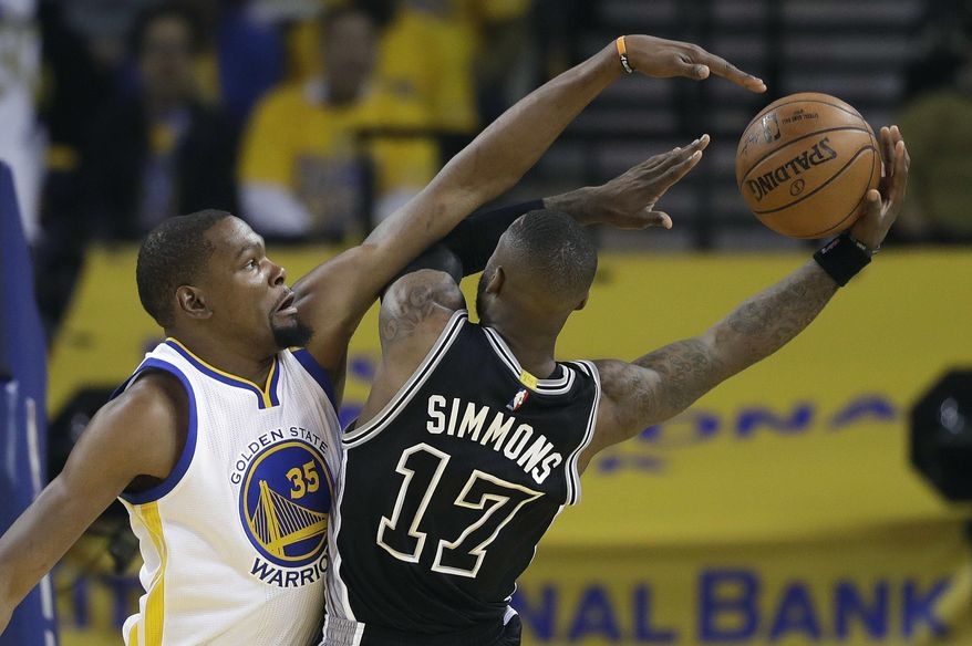 San Antonio Spurs' Jonathon Simmons (17) drives to the basket as Golden State Warriors' Kevin Durant (35) defends during the first half of Game 2 of the NBA basketball Western Conference finals, Tuesday, May 16, 2017, in Oakland, Calif. (AP Photo/Marcio Jose Sanchez)