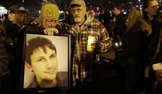 FILE - In this Dec. 5, 2016 file photo, Judy Hough, left, and her husband Brian, center, hold a picture of their son Travis, who died in a warehouse fire, during a vigil at Lake Merritt in Oakland, Calif. Attorneys representing the families of people who died in the Northern California warehouse fire that broke out during an unlicensed concert plan to file an updated lawsuit against the building's owner and manager Tuesday, May 16, 2017. (AP Photo/Marcio Jose Sanchez, File)