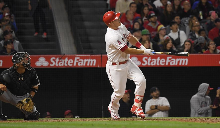 Los Angeles Angels' Mike Trout, right, hits a solo home run as Chicago White Sox catcher Kevan Smith watches during the fifth inning of a baseball game, Monday, May 15, 2017, in Anaheim, Calif. (AP Photo/Mark J. Terrill)