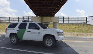 A U.S. Border Patrol vehicle passes along U.S. 281 under the West Rail Bypass International Bridge in Brownsville, Texas, Friday, May 12, 2017. Before the wall, there was the fence. And the U.S. is still paying for it. As President Donald Trump tries to persuade a skeptical Congress to fund his proposed multibillion-dollar wall on the Mexican border, government lawyers are still settling claims with Texas landowners over a border fence approved more than a decade ago. Two settlements were completed just this week. (Miguel Roberts /The Brownsville Herald via AP)