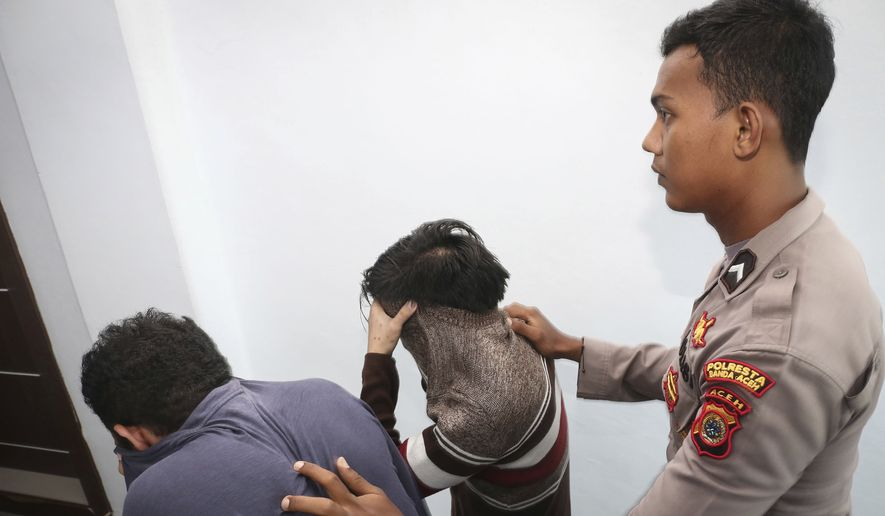 Police officer escorts two men accused of having gay sex into a holding cell to wait for the start of their trial at Shariah court in Banda Aceh, Indonesia, Wednesday, May 17,2017. A Shariah court in Indonesia's conservative Aceh province has sentenced two gay men to public caning for the first time, further tarnishing the country's moderate image after a top Christian politician was imprisoned for blasphemy. (AP Photo/Heri Juanda)