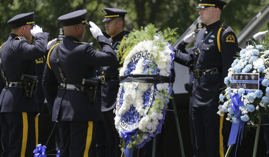 Dallas Police officers salute during a memorial service for fallen peace officers in downtown Dallas, Wednesday, May 17, 2017. The Dallas Police Department and city leaders held a ceremony to honor fallen officers as part of the annual Police Memorial Day less than a year after five officers were slain. (AP Photo/LM Otero)
