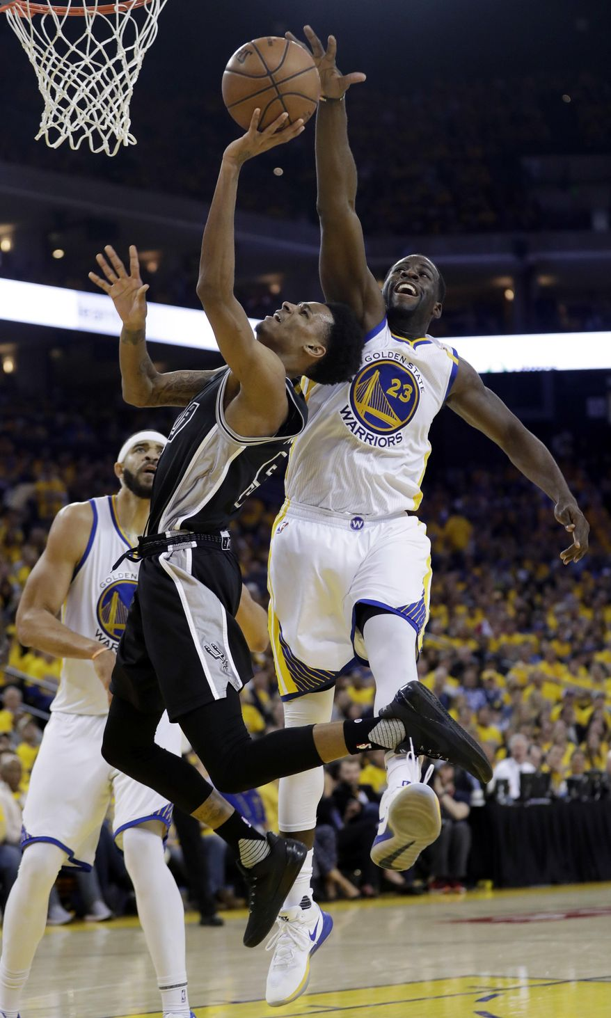 Golden State Warriors' Draymond Green (23) blocks a shot from San Antonio Spurs' Dejounte Murray during the second half of Game 2 of the NBA basketball Western Conference finals, Tuesday, May 16, 2017, in Oakland, Calif. (AP Photo/Marcio Jose Sanchez)