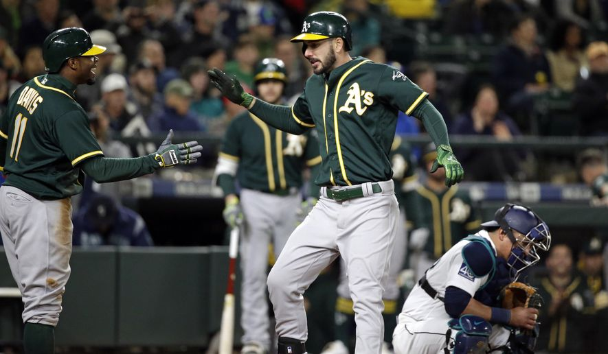 Oakland Athletics' Matt Joyce, center, shares congratulations at home on his two-run home run with Rajai Davis as Seattle Mariners catcher Carlos Ruiz looks down during the ninth inning of a baseball game Tuesday, May 16, 2017, in Seattle. (AP Photo/Elaine Thompson)