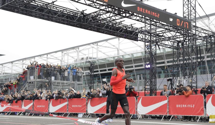 FILE - In this Saturday, May 6, 2017 file photo, Olympic marathon champion Eliud Kipchoge crosses the finish line of a marathon race at the Monza Formula One racetrack, Italy. Eliud Kipchoge was 26 seconds from making history on May 6. Nike and Adidas have announced separate plans to attack the 2-hour marathon, with both introducing shoe lines linked to the effort. Wireless tech giant Vodafone last month said it was backing a third bid, hoping data gleaned from the quest will translate into wearable technology. (AP Photo/Luca Bruno, File)