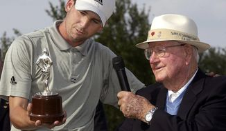 FILE - In this May 16, 2004, file photo, Sergio Garcia, of Spain, left, admires the Byron Nelson trophy as he stands next to the name sake, Byron Nelson, right, on the 18th green following Garcia's victory at the Byron Nelson Championship in Irving, Texas. Officials for the AT&T Byron Nelson and the PGA Tour announced Wednesday, May 17, 2017, that the tournament will move in 2018 to Trinity Forest Golf Club, a course located about 10 miles south of downtown Dallas that opened for play this month. The Nelson has been played at the Four Seasons Resort and Club since the TPC Las Colinas course opened there in 1983. (AP Photo/Tony Gutierrez, File)