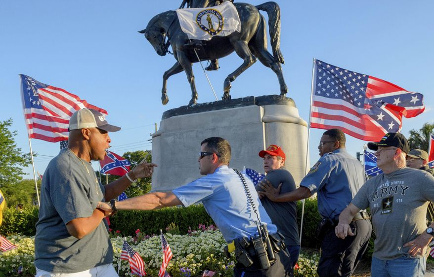 New Orleans Police separate two men after the two tussled, at the Gen. P.G.T. Beauregard monument in City Park in New Orleans, La. Tuesday, May 16, 2017. Workers in New Orleans took down a Confederate monument to Gen. P.G.T. Beauregard early Wednesday. (Matthew Hinton/The Advocate via AP)