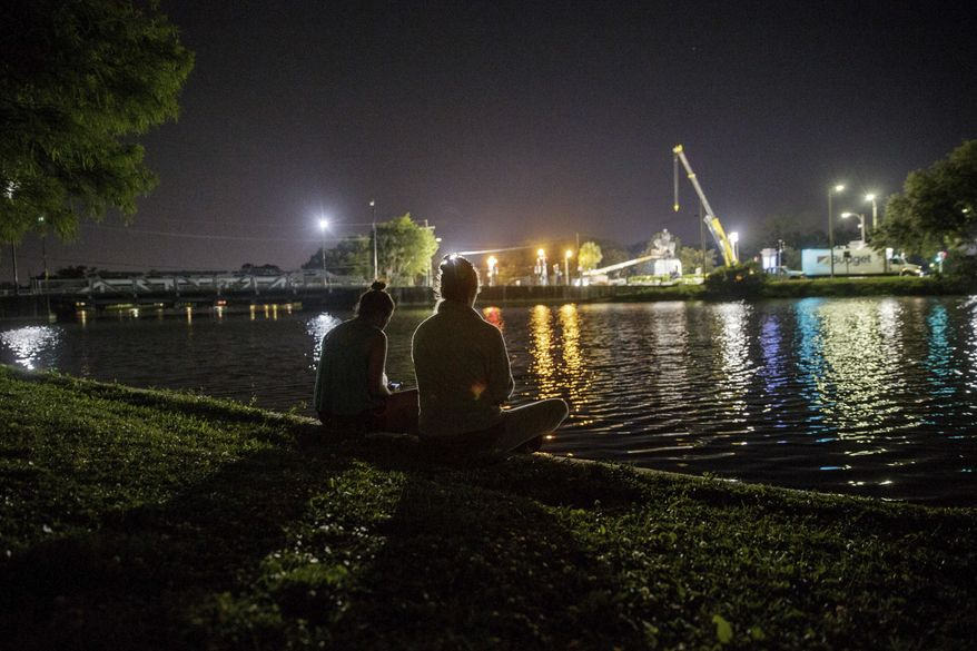 People sit along Bayou St. John to watch the removal of the General Beauregard monument from its base in New Orleans, Tuesday, May 16, 2017. Workers in New Orleans took down a Confederate monument to Gen. P.G.T. Beauregard early Wednesday. (Sophia Germer/The Advocate via AP)