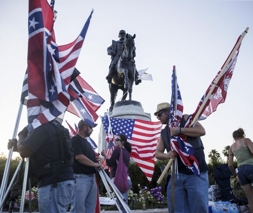 Monument supporters collect their flags before the removal of a Confederate monument to Gen. P.G.T. Beauregard in front of City Park in New Orleans, Tuesday, May 16, 2017. Workers in New Orleans took down a Confederate monument to Gen. P.G.T. Beauregard early Wednesday. (Sophia Germer/The Advocate via AP)