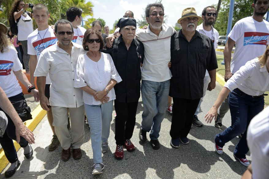 CORRECTS ORDER OF NAMES - Former prisoners, from left, Luis Rosa, Carmen Valentin, Oscar Lopez Rivera, Adolfo Matos and Luis Alberto Torres, walk with Puerto Rican nationalist Lopez to a press conference following his release from house arrest after decades in custody, on El Escambron Beach in San Juan, Puerto Rico, Wednesday, May 17, 2017. Lopez was considered a top leader of the Armed Forces of National Liberation, or FALN, an ultranationalist Puerto Rican group that claimed responsibility for more than 100 bombings at government buildings, department stores, banks and restaurants in New York, Chicago, Washington and Puerto Rico during the 1970s and early 1980s. (AP Photo/Carlos Giusti) PUERTO RICO OUT - NO PUBLICAR EN PUERTO RICO