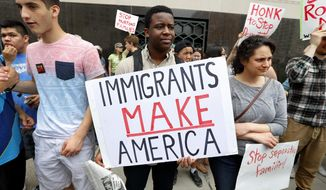 Torianto Johnson, a freshman at Pioneer High School in Ann Arbor, holds a sign supporting immigrants during a rally outside a federal courthouse in Detroit, Tuesday, May 16, 2017. Protesters rallied in hopes public outcry will again delay the deportation of Jose Luis Sanchez-Ronquillo from the United States to Mexico. (AP Photo/Paul Sancya)