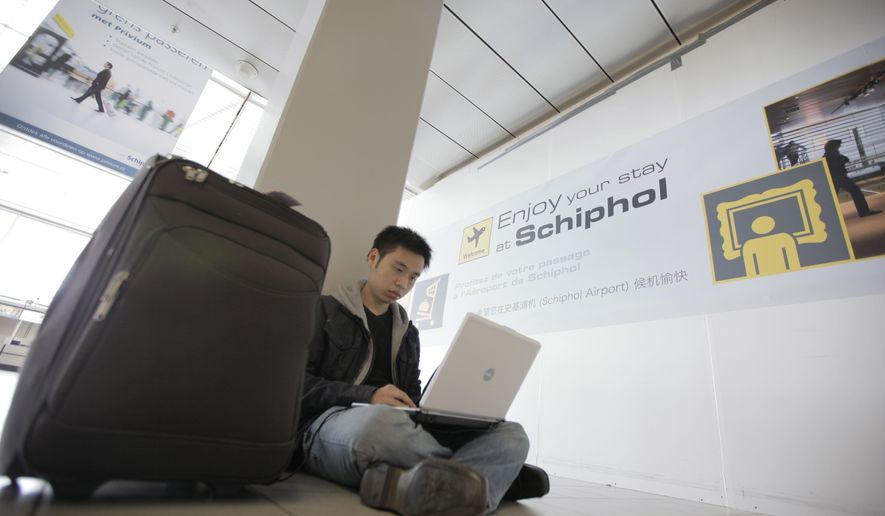 In this Saturday, April 17, 2010, photo, a traveler from Malaysia uses his laptop computer at Schiphol Airport, Amsterdam, Netherlands. International air travelers might soon rediscover magazines, paperbacks and playing cards. Airline passengers have become hooked on their laptops and tablets to get work done or just kill time during long flights. But U.S. aviation-security officials appear determined to ban large electronic devices in the cabin of flights from Europe. (AP Photo/Peter Dejong, File)