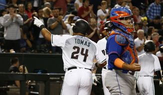 Arizona Diamondbacks' Yasmany Tomas (24) points to the crowd after hitting a home run as New York Mets' Rene Rivera, right, pauses at home plate during the sixth inning of a baseball game Tuesday, May 16, 2017, in Phoenix. (AP Photo/Ross D. Franklin)