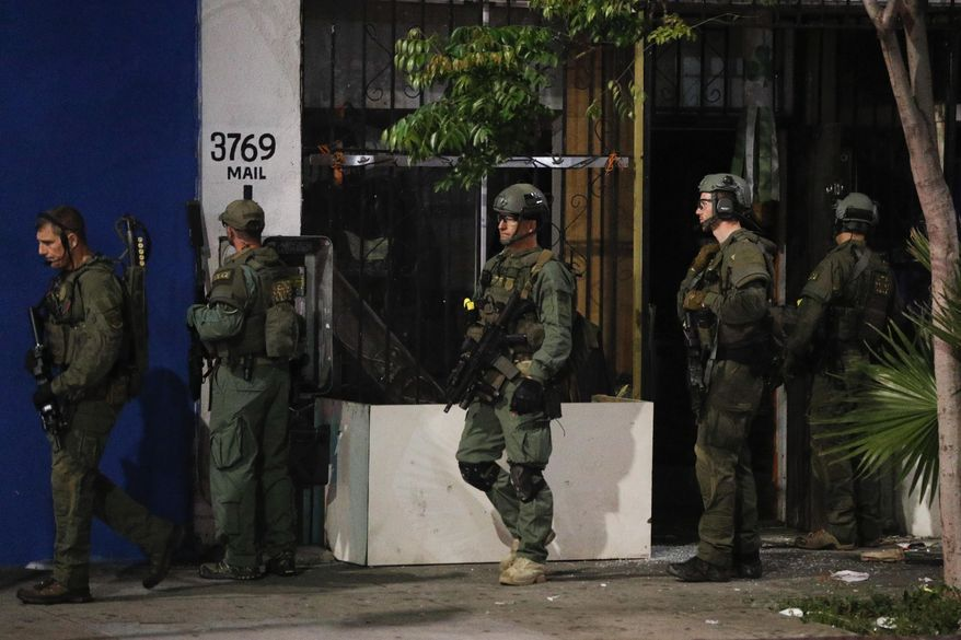 ATF agents walk out of a store after conducting a raid Wednesday, May 17, 2017, in Los Angeles. Hundreds of federal and local law enforcement fanned out across Los Angeles, serving arrest and search warrants as part of a three-year investigation into the violent and brutal street gang MS-13. (AP Photo/Jae C. Hong)