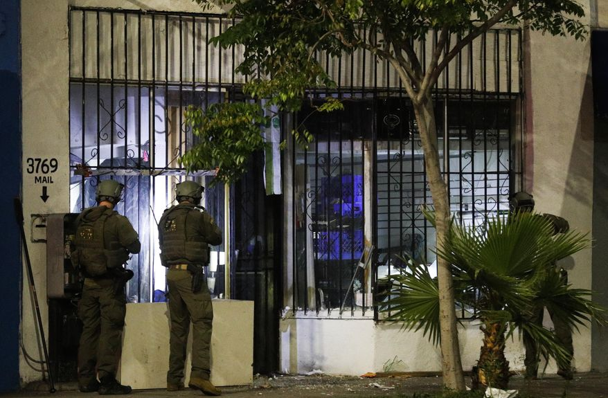 ATF agents conduct a raid early Wednesday morning, May 17, 2017, in Los Angeles. Twenty-one members and associates of MS-13 were arrested Wednesday morning as hundreds of federal and local law enforcement fanned out across Los Angeles, serving arrest and search warrants. (AP Photo/Jae C. Hong)