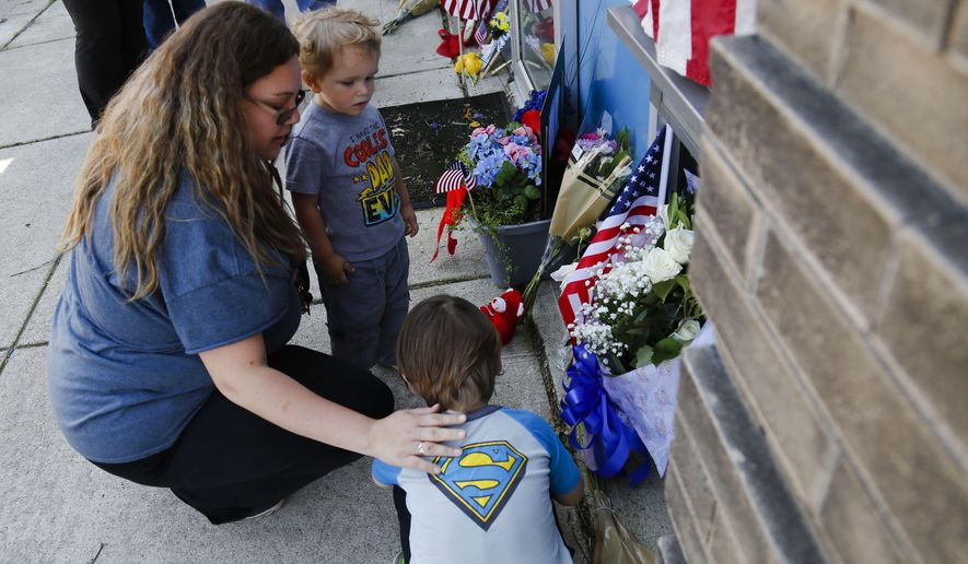 In this May 13, 2017 photo, Amanda Patterson, left, of Pataskala, Ohio, says a prayer with her sons, Connor, 4, foreground, and Samuel, 2, at a makeshift memorial outside the Kirkersville Police Department in Kirkersville, Ohio. Kirkersville police chief Steven DiSario, nurse's aide Cindy Krantz and nurse Marlina Medrano were shot and killed Friday, by Medrano's ex-boyfriend, Thomas Hartless, 43. Hartless was later found dead inside the nursing home where Medrano worked. (Joshua A. Bickel/Columbus Dispatch via AP)