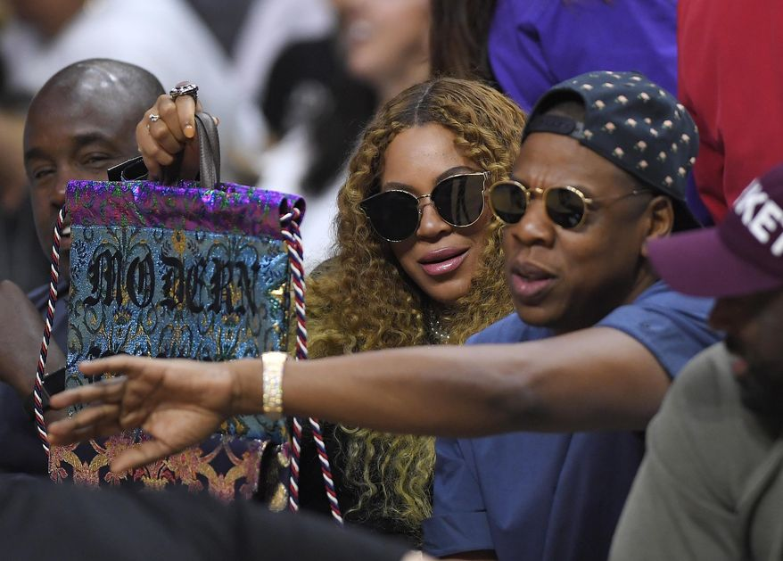 FILE - In this April 30, 2017, file photo, Beyonce and Jay Z watch during the first half in Game 7 of an NBA basketball first-round playoff series between the Los Angeles Clippers and the Utah Jazz in Los Angeles. Forbes reported on May 17, 2017, that it estimates the couple's combined wealth to be $1.16 billion. (AP Photo/Mark J. Terrill)
