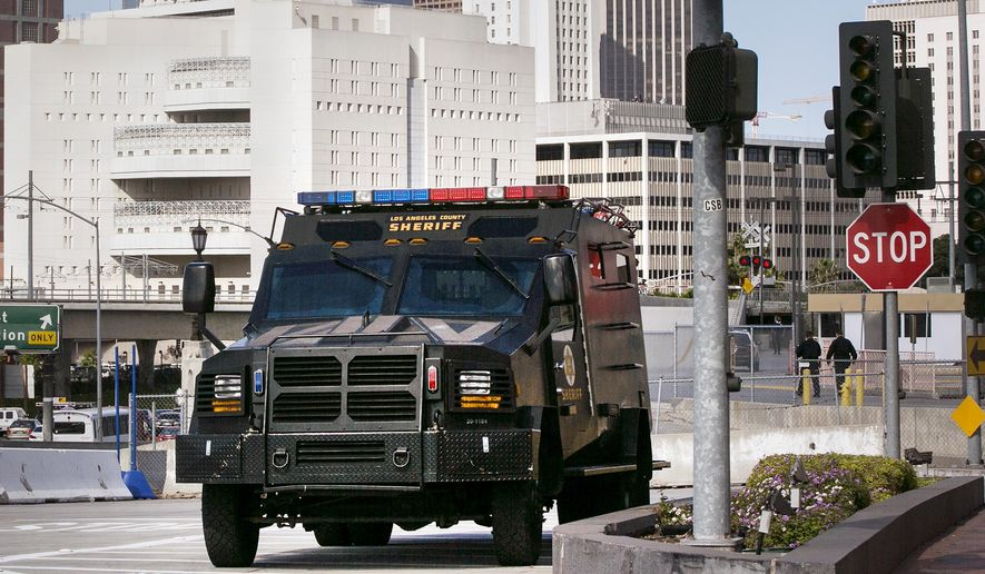 FILE - In this April 16, 2013 file photo, a Los Angeles County Sheriffs Counter Terrorism Unit armored truck is seen outside Union Station in Los Angeles, after the city increased security following deadly bombings at the Boston Marathon. Sheriff Jim McDonnell, leader of the nation's largest sheriff's department says federal officials should reconsider the curtailment of a program that provided surplus military equipment to local law enforcement. McDonnell said Wednesday, May 17, 2017 that the equipment would help ensure officers are safe when responding to active shooters and terrorist attacks. (AP Photo/Damian Dovarganes, File)