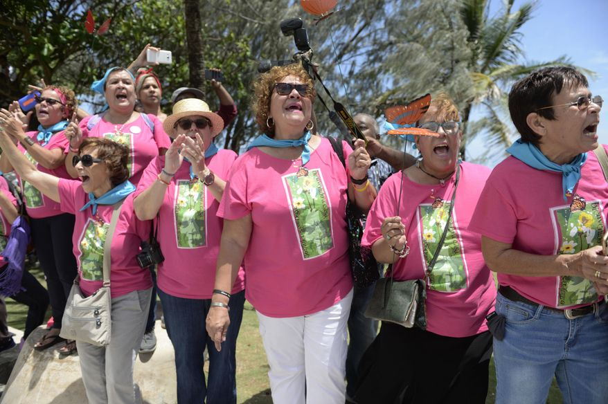 Supporters of Puerto Rican nationalist Oscar Lopez Rivera cheer as he arrives for a press conference following his release from house arrest after decades in custody, on El Escambron Beach in San Juan, Puerto Rico, Wednesday, May 17, 2017. Lopez was considered a top leader of the Armed Forces of National Liberation, or FALN, an ultranationalist Puerto Rican group that claimed responsibility for more than 100 bombings at government buildings, department stores, banks and restaurants in New York, Chicago, Washington and Puerto Rico during the 1970s and early 1980s. (AP Photo/Carlos Giusti) PUERTO RICO OUT - NO PUBLICAR EN PUERTO RICO