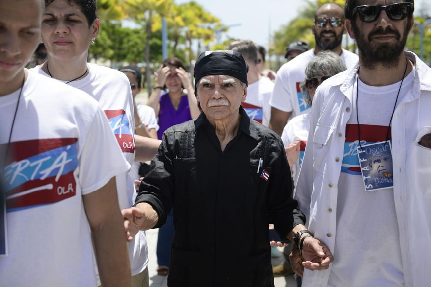 Arrival of Puerto Rican nationalist Oscar Lopez Rivera arrives for a press conference, surrounded by supporters, on El Escambron Beach following his release from house arrest after decades in custody, in San Juan, Puerto Rico, Wednesday, May 17, 2017. Lopez was considered a top leader of the Armed Forces of National Liberation, or FALN, an ultranationalist Puerto Rican group that claimed responsibility for more than 100 bombings at government buildings, department stores, banks and restaurants in New York, Chicago, Washington and Puerto Rico during the 1970s and early 1980s. (AP Photo/Carlos Giusti) PUERTO RICO OUT - NO PUBLICAR EN PUERTO RICO