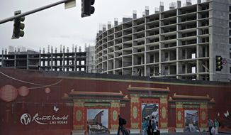 In this Tuesday, May 16, 2017, photo, people walk by the Resorts World site in Las Vegas. Malaysia-based developer Genting Group on Wednesday said the proposed 3,000-room Resorts World Las Vegas will open in 2020 after overhauling its design to have a modern Asian flair and appeal to the younger generation of gamblers. (AP Photo/John Locher)