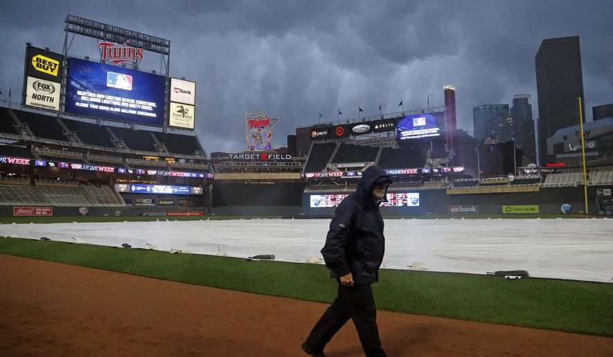 A Target Field security guard walks on field as rain delays the start of a baseball game between the Minnesota Twins and Colorado Rockies on Wednesday, May 17, 2017, in Minneapolis. (AP Photo/Jim Mone)