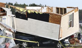 Part of a building sits on a vehicle after a tornado ripped through Prairie Lake Estates trailer home park, just north of Chetek, Wis., Tuesday, May 16, 2017. The tornado swept into the mobile home park in western Wisconsin on Tuesday, as a storm system also pounded parts of at least seven states from Texas to near the Canadian border with heavy rain, high winds and hail. (Dan Reiland/The Eau Claire Leader-Telegram via AP)