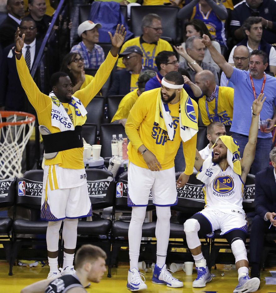 Golden State Warriors' Draymond Green, JaVale McGee and Stephen Curry, from left, celebrate from the bench in the closing minutes of the team's 136-100 win over the San Antonio Spurs during Game 2 of the NBA basketball Western Conference finals, Tuesday, May 16, 2017, in Oakland, Calif. (AP Photo/Marcio Jose Sanchez)