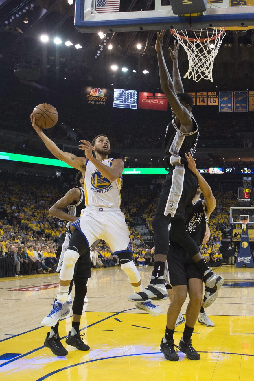Golden State Warriors' Stephen Curry, left, shoots past San Antonio Spurs' Dewayne Dedmon during the first half of Game 2 of the NBA basketball Western Conference finals, Tuesday, May 16, 2017, in Oakland, Calif. (Kyle Terada/Pool via AP)