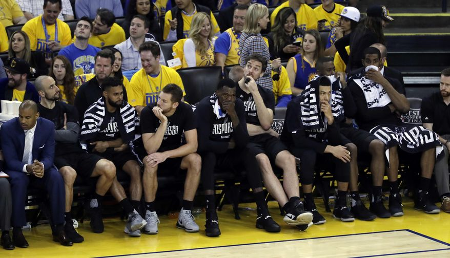 Members of the San Antonio Spurs watch from the bench in the closing minutes of the team's 136-100 loss to the Golden State Warriors during Game 2 of the NBA basketball Western Conference finals, Tuesday, May 16, 2017, in Oakland, Calif. (AP Photo/Marcio Jose Sanchez)