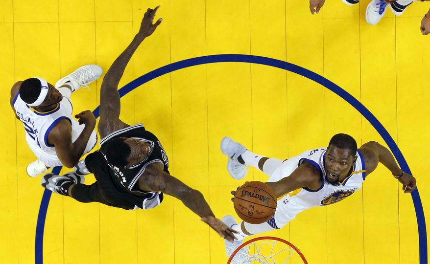 Golden State Warriors' Kevin Durant, right, works for a rebound against San Antonio Spurs' Dewayne Dedmon, center left, during the first half of Game 2 of the NBA basketball Western Conference finals, Tuesday, May 16, 2017, in Oakland, Calif. (AP Photo/Marcio Jose Sanchez)