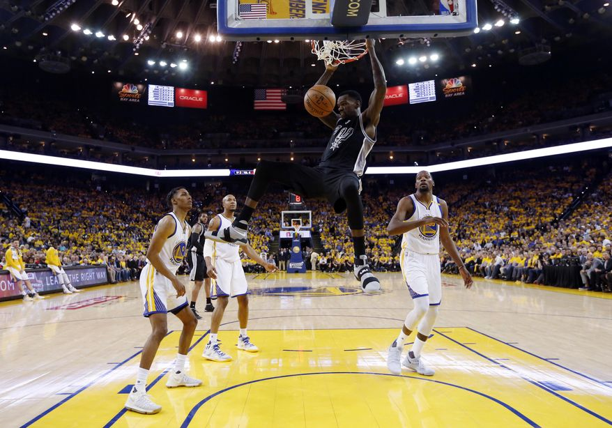 San Antonio Spurs' Dewayne Dedmon, center, dunks against the Golden State Warriors during the first half of Game 2 of the NBA basketball Western Conference finals, Tuesday, May 16, 2017, in Oakland, Calif. (Monica M. Davey/Pool via AP)