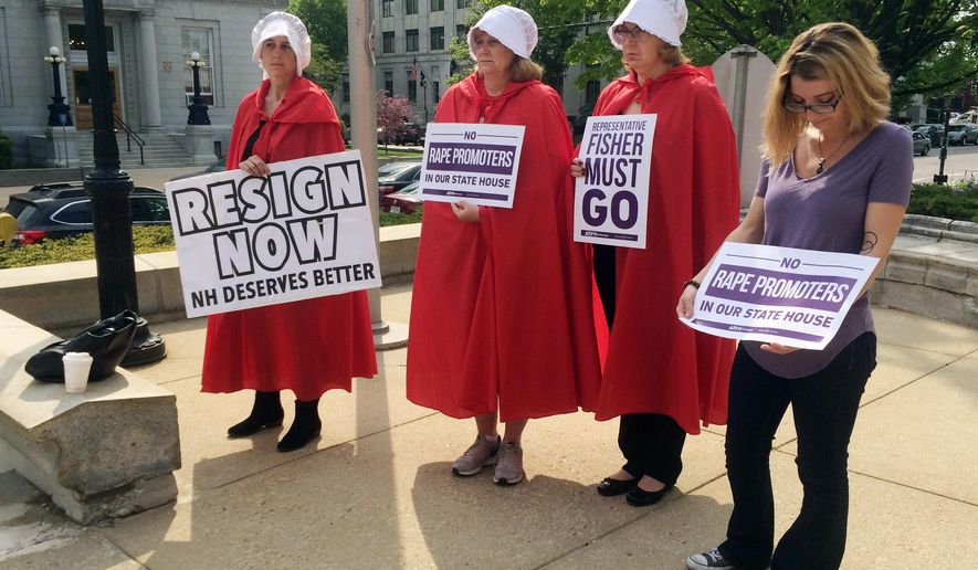 """Women dressed as characters from """"The Handmaid's Tale"""" stand outside the Legislative Office Building in Concord, N.H., Wednesday, May 17, 2017, calling for the expulsion of Republican state Rep. Robert Fisher. Under fire for creating a misogynistic online forum, Fisher resigned several hours later after a committee voted to recommend the House take no action against him. (AP Photo/Holly Ramer)"""